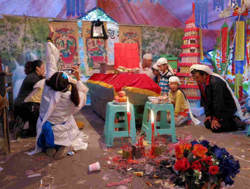 Dingding Mao and the family of the deceased kneel in front of the coffin.