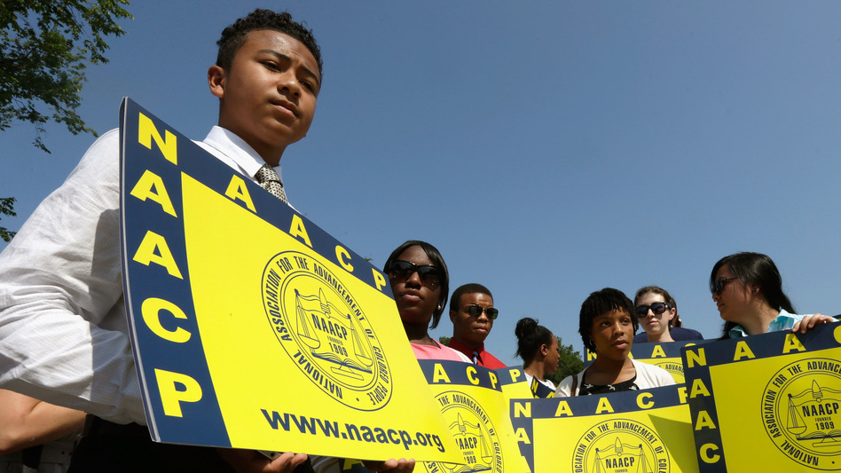Supporters of the NAACP hold signs outside the Supreme Court building on Tuesday. The court ruled that Section 4 of the Voting Rights Act, which aimed at protecting minority voters, is unconstitutional. (Getty Images)