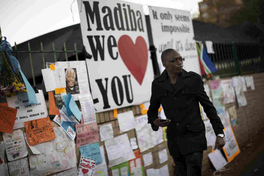 A well-wisher walks in front of a wall in Pretoria covered with messages for ailing former South African President Nelson Mandela on Wednesday.