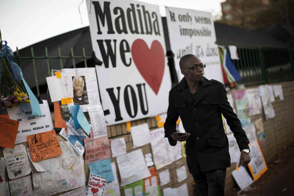 A well-wisher walks in front of a wall in Pretoria covered with messages for ailing former South African President Nelso