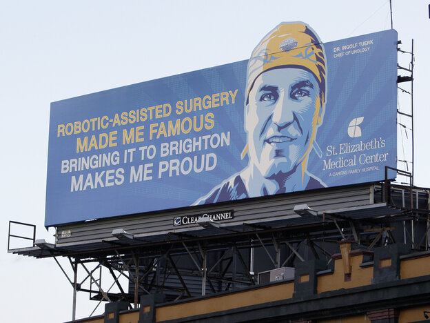 A billboard advertising robotic surgery hangs outside Boston's Fenway Park in 2009. Hospitals and doctors have heavily promoted robotic surgery.