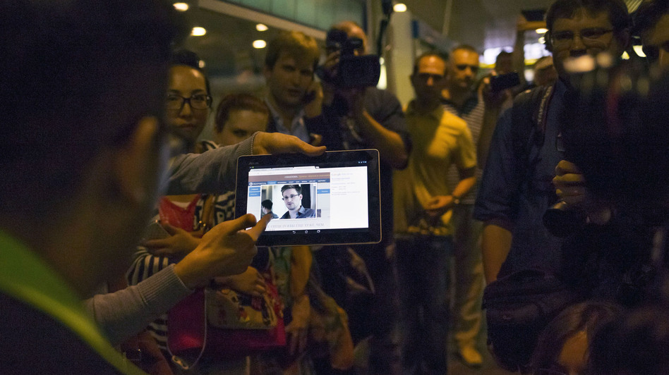 Journalists show passengers arriving at Russia's Sheremetyevo airport on Sunday an image of Edward Snowden. (AP)