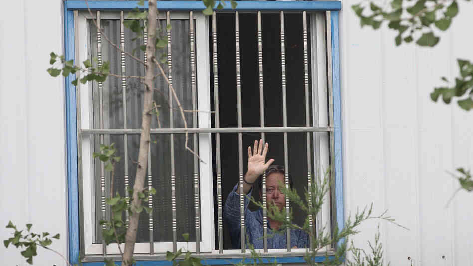 American Chip Starnes, co-owner of Specialty Medical Supplies, waves Monday from a window where he is being held by angry workers inside his plant at the Jinyurui Science and Technology Park on the outskirts of Beijing. He remained confined to the plant on Wednesday.