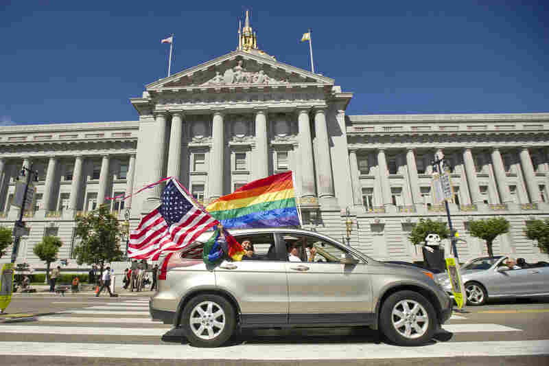 Revelers drive past San Francisco City Hall waving rainbow flags and an American flag on Wednesday shortly after the Supreme Court declared the Defense of Marriage Act unconstitutional.