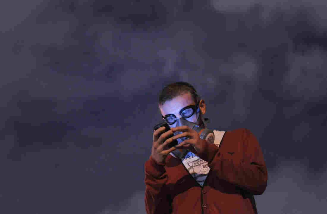 An anti-government protester wearing a gas mask uses a cellphone to read the news on social media as demonstrators gather at midnight in Istanbul's Taksim Gezi Park on June 13.