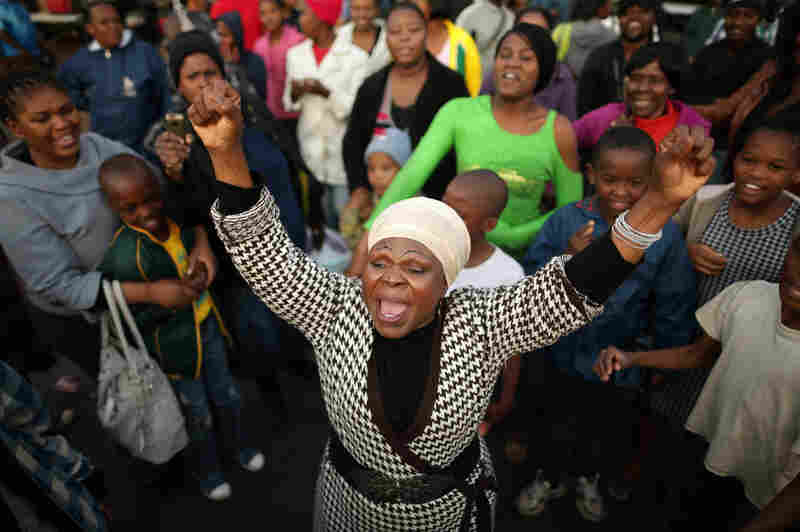 """Florence Nyadzani (center) leads people in song and cheers of support outside the hospital on June 25. """"I got my freedom because of Mandela,"""" Nyadzani said. """"We pray every day because we love him."""""""