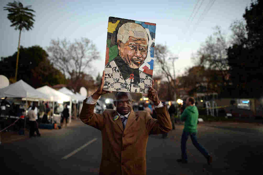 A man holds a picture as people gather to leave messages of support for former South African President Nelson Mandela outside the Mediclinic Heart Hospital in Pretoria, South Africa.