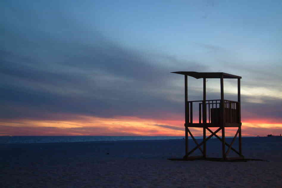 A lone lifeguard tower is caught in the final light across the sands at Gulf Shores Public Beach in Alabama.