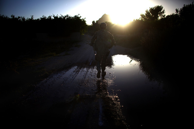 A U.S. soldier walks down a dirt road during the final U.S. patrol near the village of Arghandab, near Kandahar in southern Afghanistan. The area has long been a Taliban stronghold, and the Americans were turning the area over to the Afghan army. (NPR)