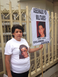 Berlin Caceres stands next to a poster with a photo of her slain son, Ebed Yanes.