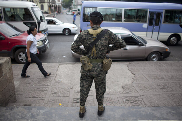 A soldier watches over public transport users during an operation in Tegucigalpa, Honduras, in April. The crime rate is soaring in Honduras, and corrupt