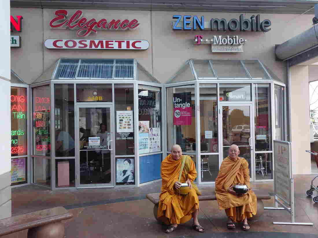 Buddhist monks sit outside a Zen Mobile store in southwest Houston.