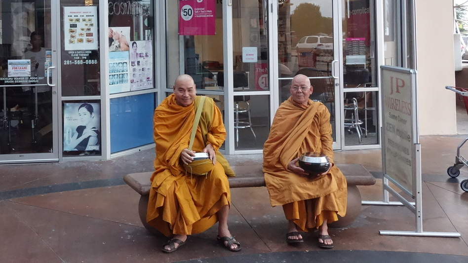 Buddhist monks sit outside a Zen Mobile store in southwest Houston. (NPR)