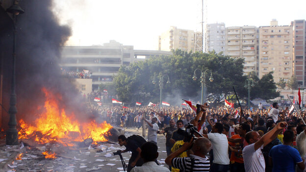 Opponents of Egypt's President Mohammed Morsi burn the contents of an office of the Freedom and Justice Party, an arm of the Muslim Brotherhood, in Alexandria Friday. Two people were reportedly kille