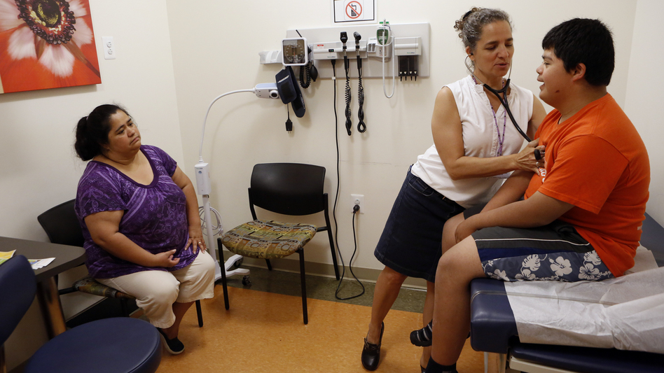 Families soon will be able to sign up for new health insurance options through the Affordable Care Act. In Washington, D.C., Dr. Cheryl Focht of Mary's Center performs a checkup of Jayson Gonzalez, 16, while his mother, Elizabeth Lopez, looks on. (NPR)