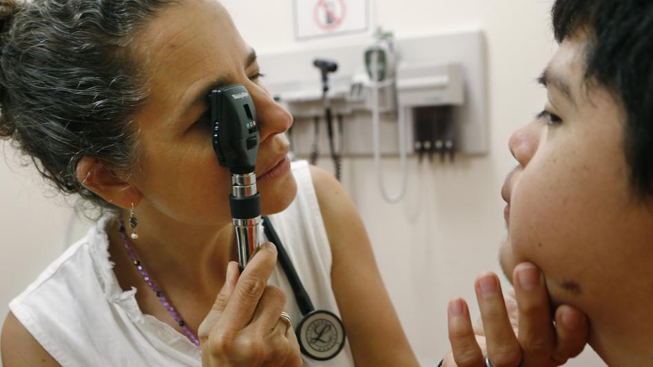 Dr. Cheryl Focht checks Jayson Gonzalez's eyes. (NPR)