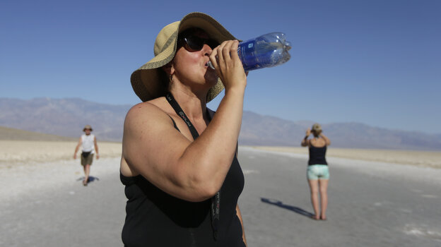 Excessive heat warnings will continue for much of the Desert Southwest through Monday. Here, Maria Wieser of Italy drinks water while sightseeing in Death Valley National Park on Friday.