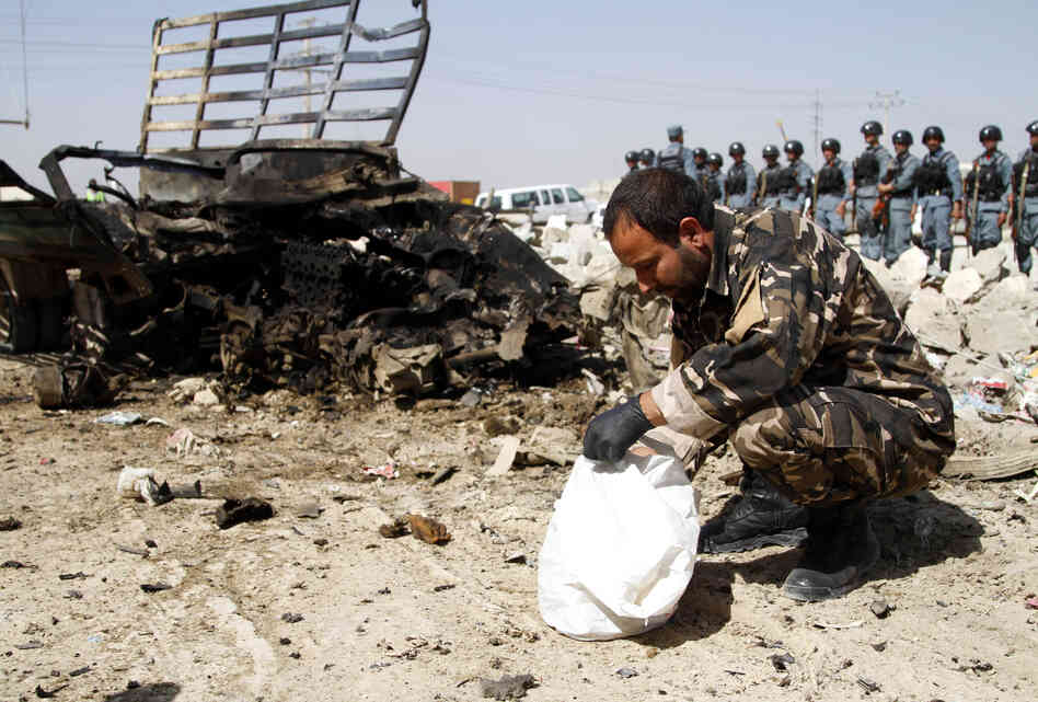 Afghan official inspects wreckage at the site of a suicide attack near Kabul military airport in Kabul, Afghanistan, on June 10. After a month outside the country, NPR's Sean Carberry returned to find some things that had changed, but many, like insurgent violence, that remain the same.