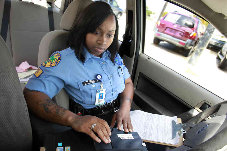 Miami Public Service Aide Tatayana Harris enters information into her laptop after clearing an accident in Miami's Little Havana community. Harris has been a Miami Police PSA for fiv