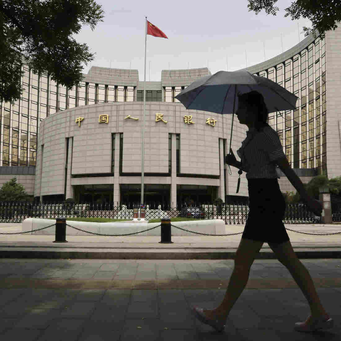 A woman walks past the headquarters of the People's Bank of China (PBOC), the central bank, in Beijing.