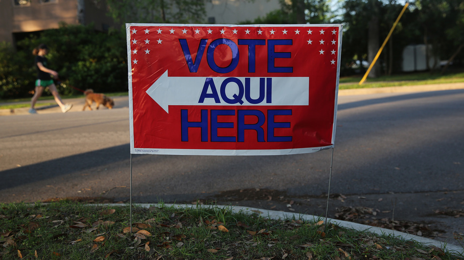 A bilingual sign stands outside a polling center at a public library ahead of local elections on April 28 in Austin, Texas. (Getty Images)