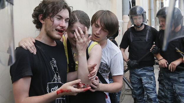 Riot police guard gay rights activists who were beaten by anti-gay protesters during an authorized gay rights rally in St. Petersburg, Russia, on Saturday. While a march there was allowed to go ahead, gay rights activists in Moscow turned to the Web on Sunday to celebrate gay pride.
