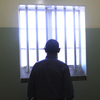 President Obama looks out the window of the Robben Island prison cell that once held Nelson Mandela. The president and his family visited the prison on Sunday.