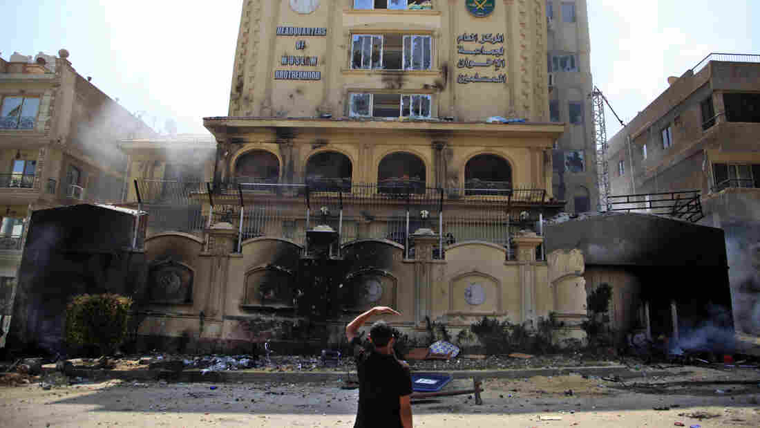 An Egyptian protester looks at the damaged Muslim Brotherhood headquarters in Cairo. Protesters stormed and rans