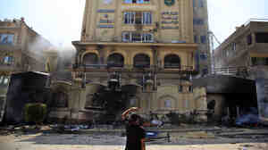 An Egyptian protester looks at the damaged Muslim Brotherhood headquarters in Cairo. Protesters stormed and ransacked the headquarters early Monday, in an attack that