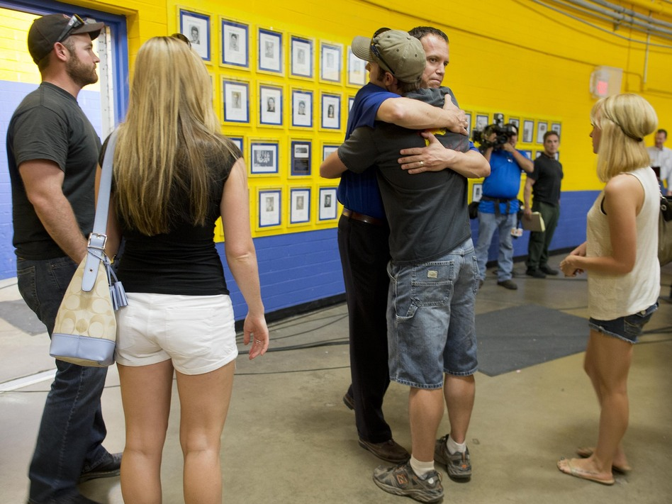 Members of the Prescott fire department embrace Monday as they arrive to listen in at a news conference in Prescott, Ariz.
