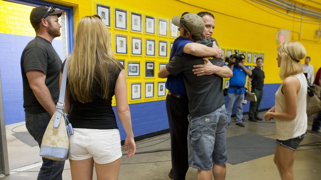 Members of the Prescott fire department embrace Monday as they arrive to listen in at a news conference in Prescott, Ariz. (AP)