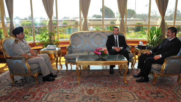"""Before The Fall: Then-Egyptian President Mohammed Morsi (right) met Monday with Prime Minister Hesham Kandil (center) and Defense Minister Gen. Abdel-Fattah al-Sisi in Cairo. Since then, the military has ousted Morsi, suspended the constitution and imposed a """"road map"""" for political transition in Egypt after the president refused calls to step down. (Xinhua/Landov)"""