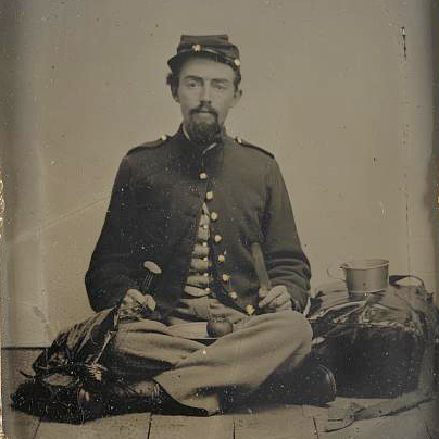 This unidentified Union soldier is preparing to eat a slice of the apple on his lap.