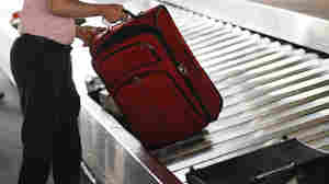 A traveler collects his bag from a luggage carousel in the Ph