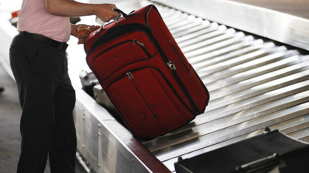A traveler collects his bag from a luggage carousel in the Philadelphia International Airport in 2011. Baggage fees have helped financially desperate carriers stay aloft. (AP)