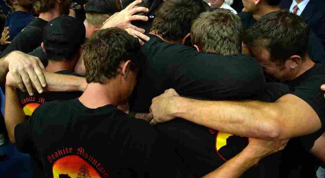 Holding on to each other:  Firefighters hug during a memorial service Monday in Prescott, Ariz. They were honoring 19 others who died Sunday.