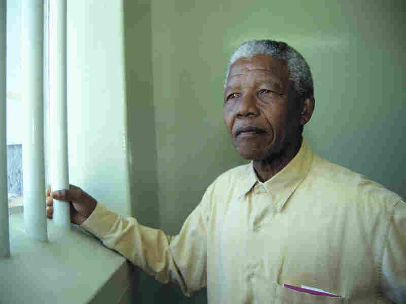 Mandela and other inmates faced harsh conditions during his many years at Robben Island prison. In the final year of his detention, the South African authorities put him in a private cottage where he had a swimming pool and a cook. Mandela is shown here during a return visit to his old Robben Island cell in 1994.