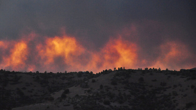 Flames from the Doce Fire rise above a hillside in Arizona's Prescott National Forest at dusk on June 18.