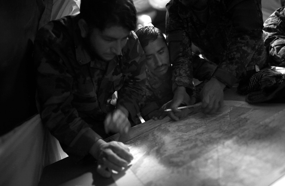 ANA soldiers plot coordinates on a map with the help of their American trainers. (NPR)