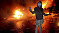 Alexandria, Egypt: A masked protester poses with a tear gas canister in front of a burning vehicle during clashes between opponents of Egyptian President Mohammed Morsi and his Islamist supporters on Dec. 21, 2012.