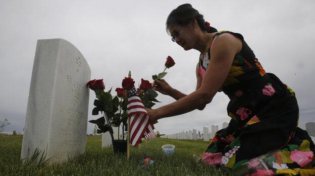 Karen Jang places flowers on the the grave of her late boyfriend, Vietnam veteran Francis Yee, during her Memoria