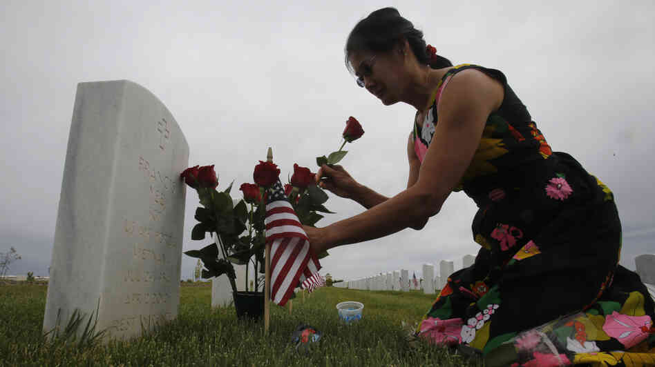 Karen Jang places flowers on the the grave of her late boyfriend, Vietnam veteran Francis Yee, during her Memorial Day visit to the