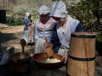 Emma Dodd and Claire Quinn, churn butter at  Claude Moore Colonial Farm.