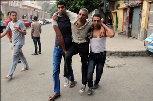 Two men help an injured protester as supporters and opponents of the president clash outside Cairo University.