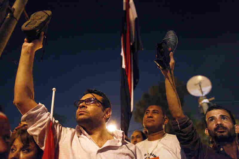 Protesters watch Morsi's speech near the presidential palace in Cairo. Morsi told Egyptians that he had been freely elected a year ago, and that he intends to carry out his duties.