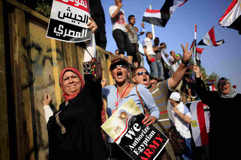 "Morsi opponents chant slogans during a protest outside the presidential palace, in Cairo. The poster with partial translation of Arabic reads, ""We support the Egyptian military."""
