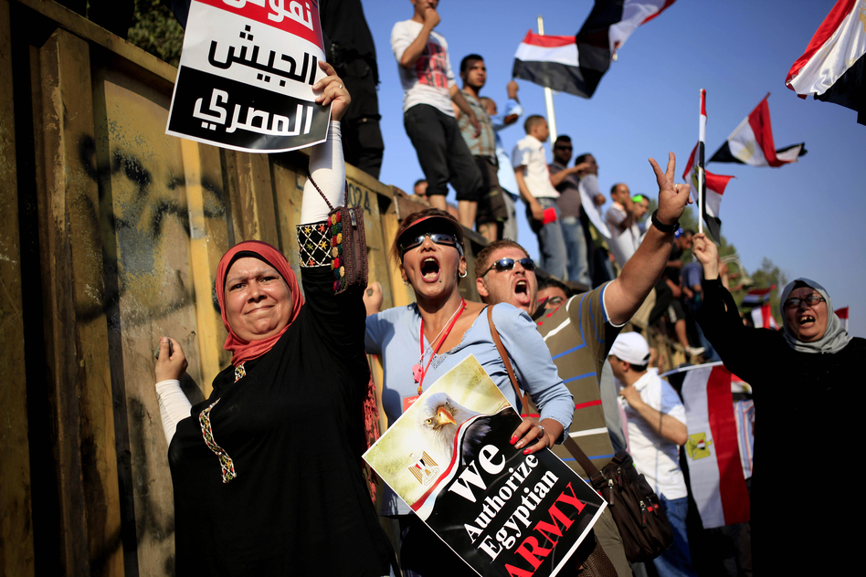 "Morsi opponents chant slogans during a protest outside the presidential palace, in Cairo. The poster with partial translation of Arabic reads, ""We support the Egyptian military."" (AP)"