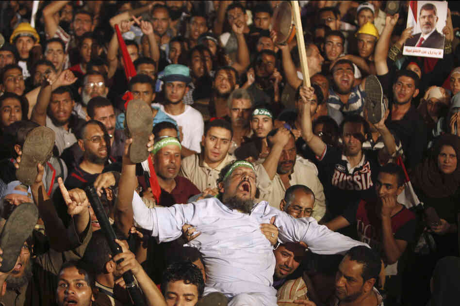 "Members of the Muslim Brotherhood and supporters of Morsi react after the Egyptian army's statement outing Morsi, at the Raba El-Adwyia mosque square in Cairo. Morsi responded via twitter that his removal ""represent[s] a full coup categorically rejected by all the free men of our nation."""