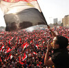 Protesters opposing Egyptian President Mohammed Morsi wave flags in Tahrir Square in Cairo on Wednesday. Shortly afterward, the military staged a coup, ousting Morsi and suspending the constitution.