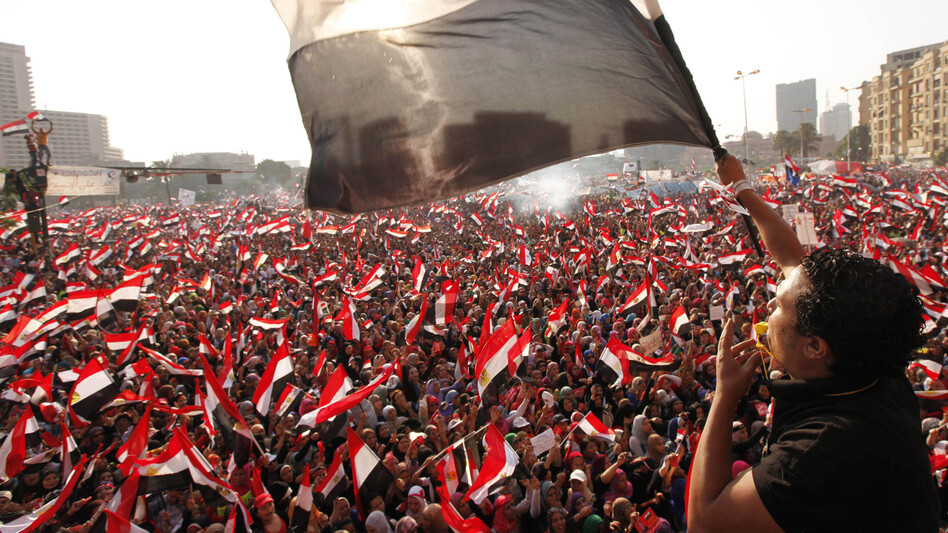 Protesters opposing Egyptian President Mohammed Morsi wave flags in Tahrir Square in Cairo on Wednesday. Shortly afterward, the military staged a coup, ousting Morsi and suspending the constitution. (Reuters/Landov)